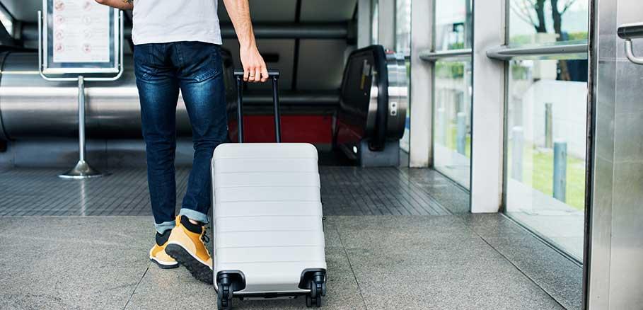 Άντρας που σέρνει βαλίτσα μετά από ταξίδι.