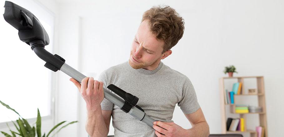 Ξανθός άντρας με γκρι μπλούζα κρατάει ηλεκτρική σκούπα βασικό εργαλείο για καθαρισμό στρώματος από ακάρεα