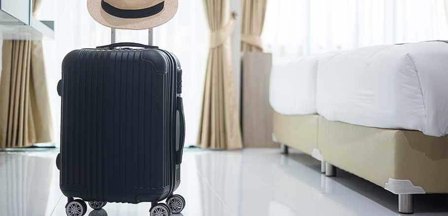 Μαύρη βαλίτσα με ρόδες και ψάθινο καπέλο σε δωμάτιο ξενοδοχείου