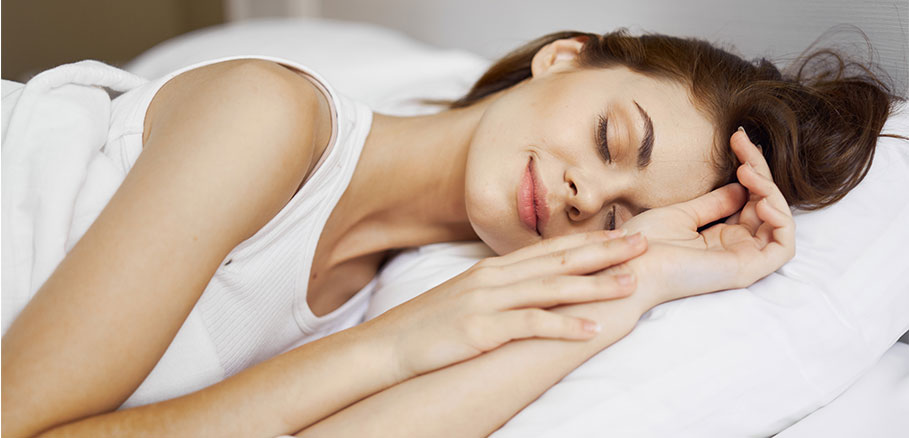 Νεαρή γυναίκα κοιμάται χαμογελαστή σε καθαρό κρεβάτι