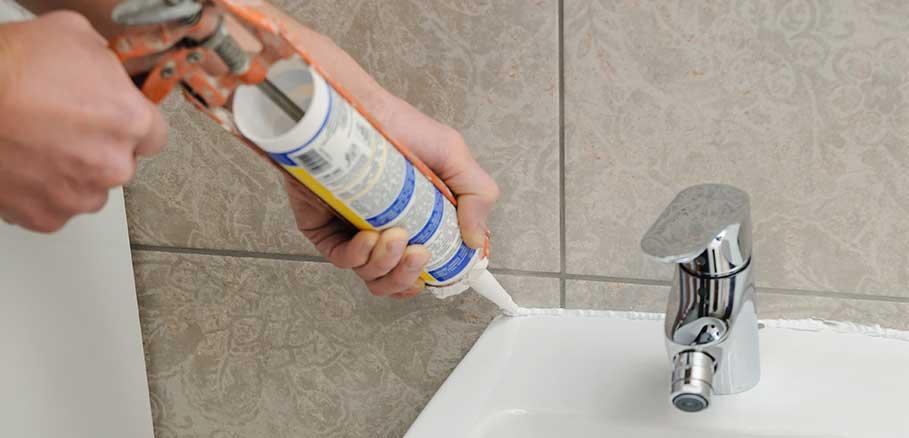 Άντρας κλείνει ρωγμές σε νιπτήρα μπάνιου με εργαλείο σιλικόνης
