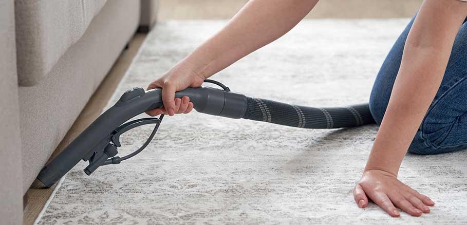 Γυναίκα καθαρίζει με ηλεκτιρκή σκούπα κάτω από καναπέ. Βασικός τρόπος αντιμετώπισης για ασημόψαρο
