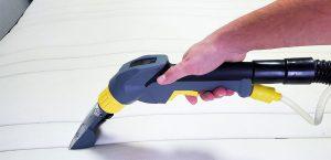 Χέρι άντρα καθαρίζει κρεβάτι με ηλεκτρική σκούπα, λύση στο ερώτημα πώς να καθαρίσω το στρώμα από ακάρεα