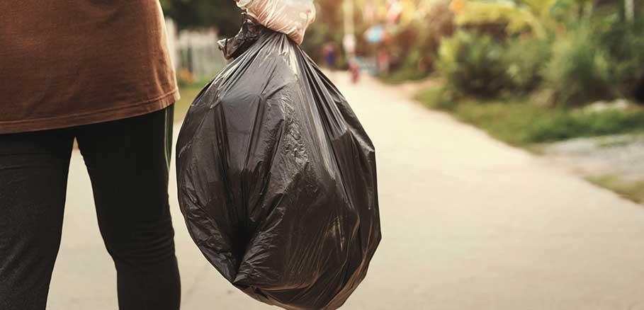 Γυναίκα πάει να πετάξει μαύρη σακούλα σκουπιδιών