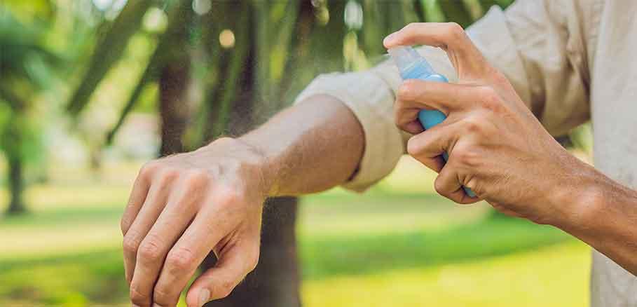 Άντρας ψεκάζει αντικουνουπικό σπρέι στον καρπό του χεριού του.